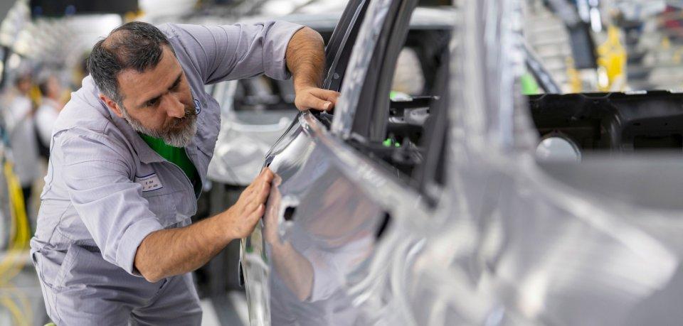 Ein VW-Mitarbeiter baut in Wolfsburg am neuen VW Golf 8.