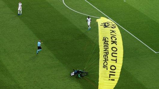 Der Greenpeace-Aktivist landet unsanft auf das Spielfeld. Auf dem Bild sieht man noch die DFB-Nationalspieler Mats Hummels und Antonio Rüdiger.