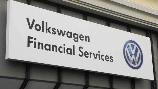 Ein Volkswagen Financial Services-Schild hängt an einer Hausfassade.