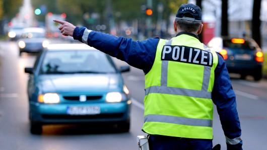 Ein Polizist winkt ein Auto raus. (Archivbild)