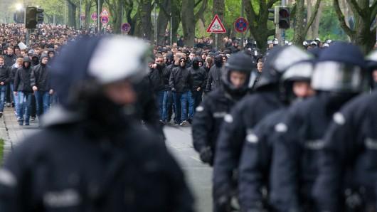 Polizisten begleiten den farbenfrohen Fanzug von Hannover 96 zum Stadion (Archivbild).