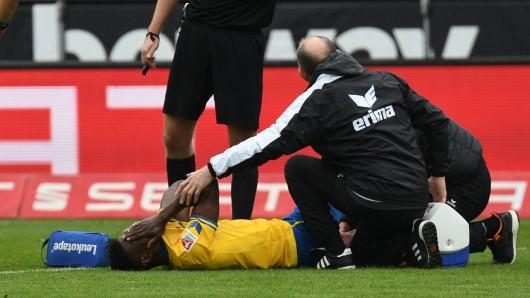 Braunschweigs Joseph Baffo liegt verletzt am Boden und wird behandelt.