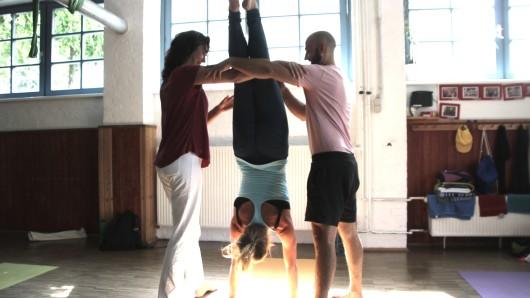 Probieren sich beim Handstand-Yoga: Susanna von der Yoga-Schule Behmke-Haiduk, Stella aus der Yoga-Schule Varas und Kursleiter Niels von der Yoga-Schule Solis (v.l.).