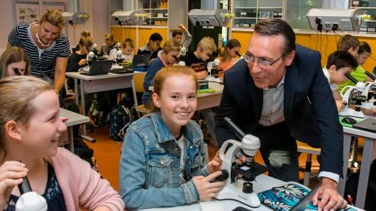 Andreas Hartmann, Geschäftsführer der SE|BS, schaut den Schülern der Raabeschule bei seinem Besuch über die Schulter. Biologie-Lehrerin Tanja Zimmermann (hinten) freut sich mit den Kindern über die neuen Mikroskope.
