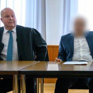 Ein Arzt (rechts) und sein Anwalt Jürgen Hoppe sitzen in einem Saal im Landgericht Braunschweig.