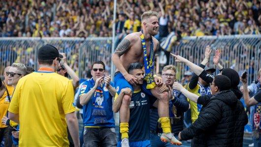 Erlösung bei Eintracht Braunschweig: Onur Bulut nimmt seinen Kumpel Felix Burmeister auf die Schulter – und zeigt damit auch, was er von dem umstrittenen Banner in Block 9 hält.