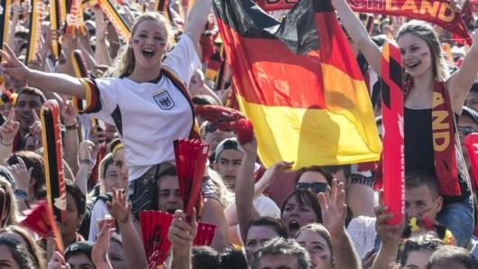 Fans stehen auf der Fanmeile und verfolgen ein Spiel der deutschen Mannschaft.
