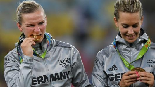 Alexandra Popp und Lena Goeßling prüfen die Medaillen auf ihre Echtheit.