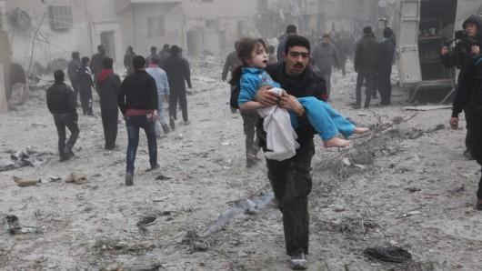 Ein Mann trägt nach einem Angriff auf Aleppo ein Mädchen weg. (Archivbild)