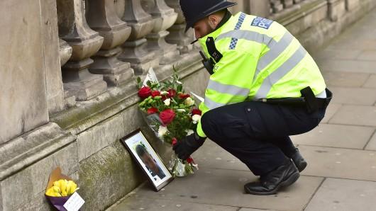 Ein Polizist legt Blumen in Erinnerung an seinen getöteten Kollegen nieder.