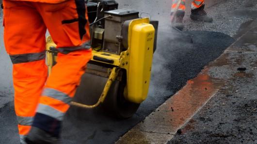 Mitarbeiter des Straßen- und Tiefbauamt beseitigen Schlaglöcher auf einer Straße.