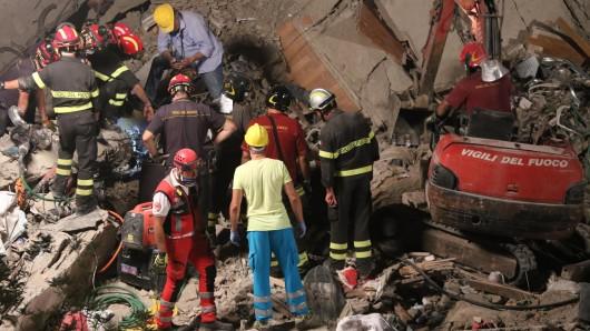 Rettungskräfte arbeiten sich durch das Geröll eines zusammengestürzten Gebäudes in Torre Annunziata in Italien.