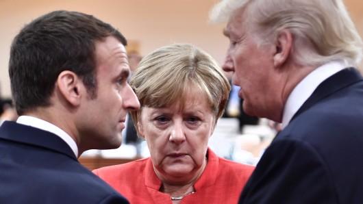 US-Präsident Donald Trump (rechts) im Gespräch mit seinem französischen Amtskollegen Präsident Emmanuel Macron. Kanzlerin Merkel (CDU) hört zu.