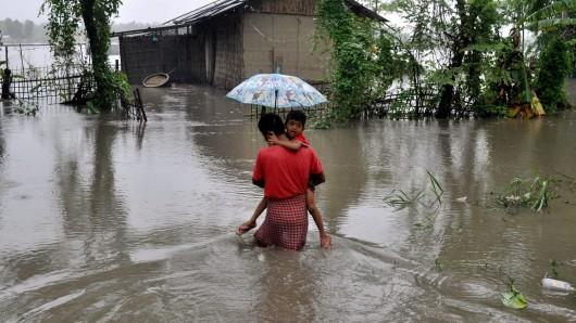 Ein Vater trägt in Lakhimpur (Indien) seinen Sohn und watet durch ein überflutetes Gebiet.