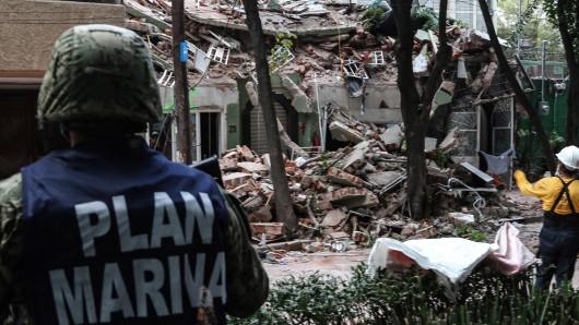 Rettungskräfte stehen vor den Trümmern eines eingestürzten Hauses in Mexiko-Stadt.