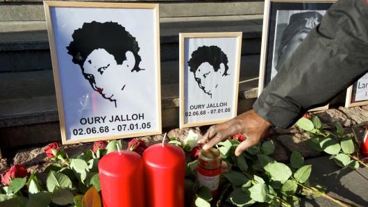 Rosen liegen vor dem Bild von Oury Jalloh am Hauptbahnhof in Dessau-Roßlau. (Archivbild)