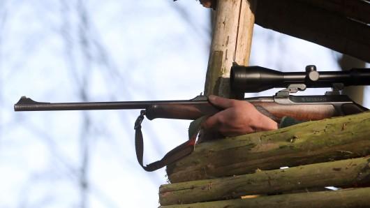 Auf dem gestellten Foto sitzt ein Jäger nach einer Treibjagd auf einem Hochsitz mit seinem Jagdgewehr. (Symbolbild)