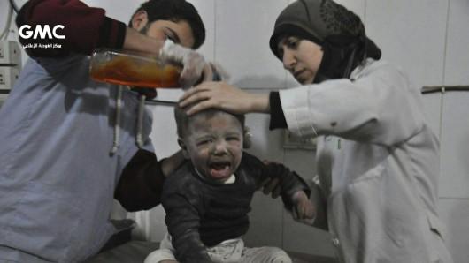 Ein von regierungskritischen Aktivistengruppe Ghouta Media Center zur Verfügung gestelltes und durch Abgleich mit AP-Berichterstattung authentifiziertes Bild zeigt zwei Ärzte, die einen syrischen Jungen versorgen, der während des Angriffs der syrischen Luftwaffe verwundet worden ist.