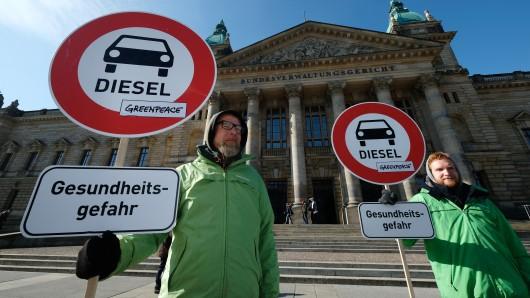 Umweltaktivisten stehen mit Schildern vor dem Bundesverwaltungsgericht. Fahrverbote für Dieselfahrzeuge in besonders belasteten deutschen Städten können ein rechtlich zulässiges Mittel sein, um Luftreinhaltepläne einzuhalten.