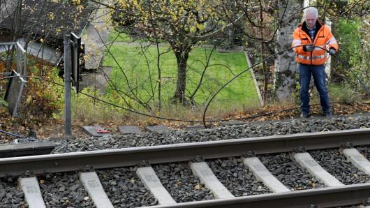 Ein Servicetechniker der Deutschen Bahn ist nach einem Brand in einem Kabelschacht entlang einer Bahnlinie mit der Reparatur einiger verschmorter Leitungen beschäftigt. (Archivbild)