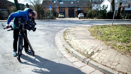 Ein Kameramann filmt den Tatort eines Messerangriffs an einer Abzweigung in einem Wohngebiet (Archivbild).