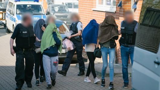 Polizisten führen Frauen aus einem Haus . Im Fokus stehen gefälschte Visa, Menschenhandel, Zuhälterei und Zwangsprostitution von Thailänderinnen, wie die Bundespolizei in Stuttgart sagte.
