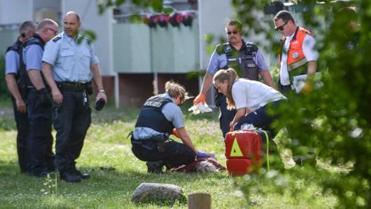 Nach einem Messerangriff auf eine Frau liegt der mutmaßliche Täter auf einer Wiese und wird von Polizei und Rettungskräften versorgt.