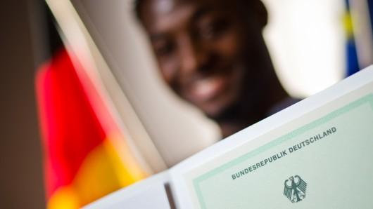 Ein Mann aus Kamerun posiert bei einer Einbürgerungszeremonie für Erinnerungsfotos mit einer Einbürgerungsurkunde der Bundesrepublik Deutschland (Archivbild).