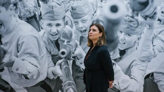 Cordula Lebeck, Witwe des Fotografen Robert Lebeck steht in der Ausstellung Robert Lebeck 1968. Im Hintergrund ein Bild von Kinderkadetten in einer amerikanischen Militärakademie.