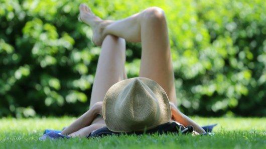 Eine Frau entspannt sich im Freibad im Schatten eines Baumes.