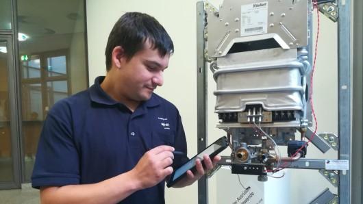 Techniker Sascha Sander vor einem Gas-Gerät. Ob die nötigen Ersatzteile vorhanden sind, liest er in einer Datenbank ab.