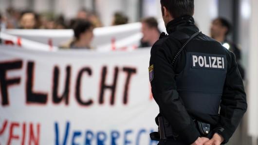 Ein Polizist überwacht eine Demo von Abschiebungsgegnern (Archivbild).