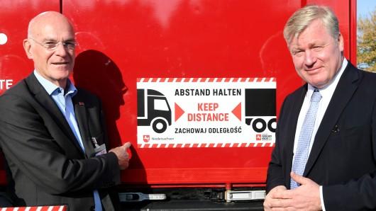 Verkehrsminister Bernd Althusmann (CDU, rechts), und Heiner Bartling, Präsident der Landesverkehrswacht Niedersachsen, stehen an einem am Lastzug angebrachten, dreisprachigen Aufkleber zum Abstand halten.