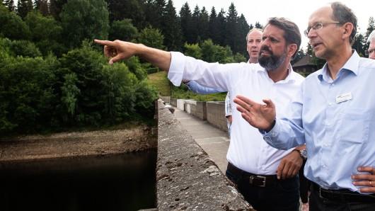 Olaf Lies (links, SPD), Umweltminister von Niedersachsen, steht während seiner Sommerreise mit Andreas Lange, Bereichsleiter Betrieb der Harzwasserwerke, auf der Staumauer der Eckertalsperre im Harz.