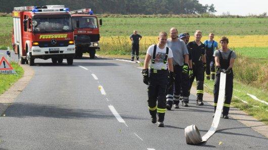 Feuerwehrleute verlegen Schläuche, um Löschwasser zum betroffenen Testgelände der Bundeswehr zu bringen (Archivbild).