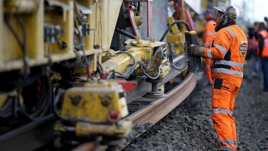 Ein Arbeiter überwacht an einem Gleisumbauzug die Verlegung neuer Schienen (Archivbild).