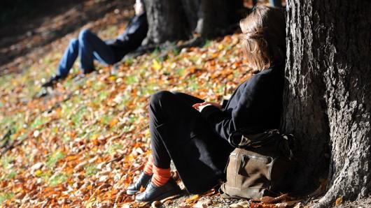 Eine junge Frau genießt die Herbstsonne (Symbolbild).