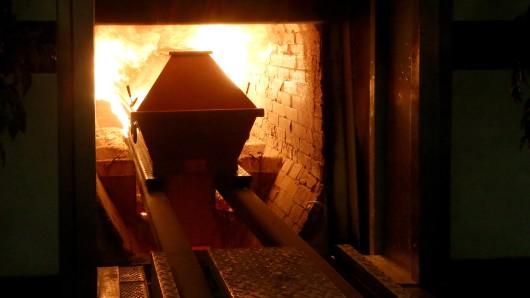 Ein Sarg wird in den rund 850 Grad heißen Krematoriumsofen gefahren.  (Symbolbild)
