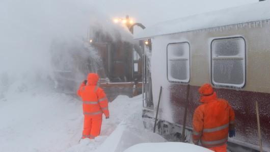 Mitarbeiter der Servicegesellschaft versuchen einen Zug der Harzer Schmalspurbahn, der seit Montag auf dem Brocken eingeschneit ist, vom Schnee zu befreien.