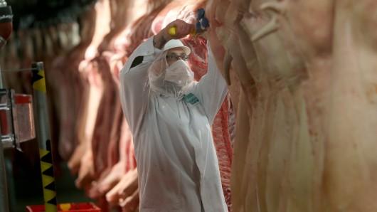 Ein Schlachthof-Mitarbeiter bearbeitet Schweinehälften (Symbolbild).