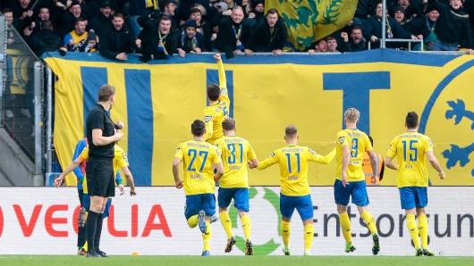 Benjamin Kessel lässt sich nach seinem Tor für EIntracht Braunschweig gegen Hansa Rostock von den Fans und seinen Mitspielern feiern.
