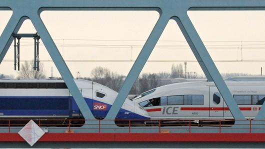 Ein TGV und ein ICE (r) stehen auf einer Rheinbrücke. Die EU-Wettbewerbshüter werden die geplante Bahn-Fusion von Siemens und dem französischen Konkurrenten Alstom offenbar untersagen.