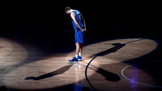Dirk Nowitzki von den Dallas Mavericks steht nach dem Spiel auf dem Spielfeld und hört ehemaligen Spielern zu, die eine Laudatio auf ihn halten.