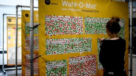 Eine junge Frau klebt einen Sticker in einem Wahllokal am Rande der U18-Europawahl an eine Wahl-O-Mat Wand.