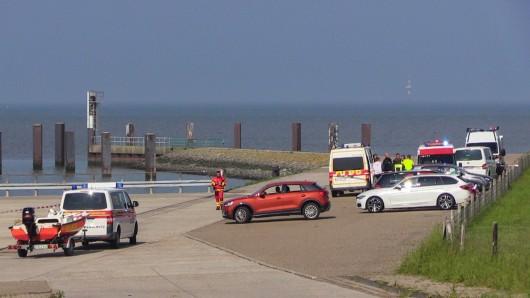Helfer der Deutschen Lebens-Rettungs-Gesellschaft stehen bei einer Suchaktion auf einem Parkplatz neben der Nordsee. Auf dem Weg von Wangerooge nach Hannover ist ein Kleinflugzeug abgestürzt. Bei einer Suchaktion am Jadebusen wurden jetzt Wrackteile gefunden.