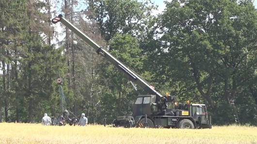 Mit einem Autokran werden an der Absturzstelle eines Hubschraubers nahe Aerzen Wrackteile geborgen.