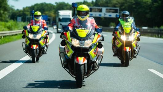 Drei Johanniter-Stauhelfer fahren mit ihren Motorrädern auf der Autobahn. Die Motorradstaffel der Johanniter ist an heißen Tagen mit ihren ehrenamtlichen Fahrern auf den Autobahnen unterwegs und hilft Autofahrern.
