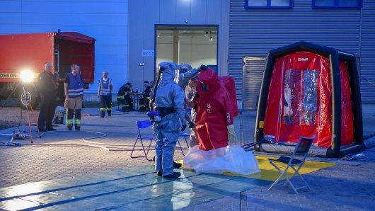 Einsatzkräfte in Schutzanzügen sind in einem Gewerbegebiet in dem Schwefelsäure ausgetreten war im Einsatz.
