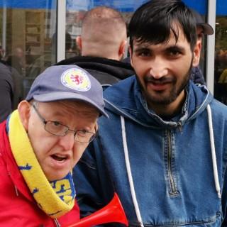 Obaidullah Zaim (rechts, Ehrenamtlicher aus Afghanistan) hilft Thorsten Walter (Lebenshilfe Braunschweig) beim Besuch im Eintracht-Stadion.