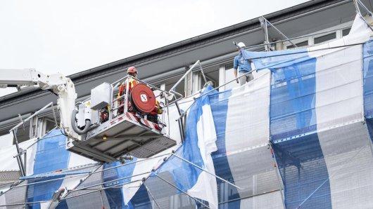 Feuerwehrmänner sichern ein Baugerüst auf dem Dach des Finanzamts in Hannover. Durch eine Sturmböe wurden Teile eines 20 Meter hohen Baugerüsts an der Fassade des Finanzamt-Mitte aus den Halterungen gedrückt.